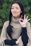 De mooie jonge gelukkige vrouw knipoogt en toont als o.k. in het bos dichtbij de dag van de bomenwinter Stock Foto's