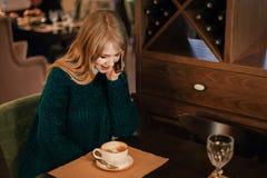De mooie jonge glimlachen van de blondevrouw bij koffiewinkel en besprekingen op telefoon stock foto's