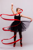 De mooie jonge het balletturner van de blondevrouw oefening van opleidingscalilisthenics met rood lint met rode schoenen stock afbeelding