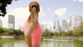De mooie jonge jogging van de vrouwenagent in park Geschikte vrouwelijke sportfitness opleiding Het genieten van de van mening stock videobeelden