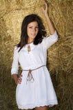 De mooie jonge landbouwbedrijfvrouw dichtbij een stro verpakt muur in balen Stock Afbeelding
