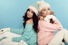 De mooie jonge meisjes met krullend haar draagt comfortabele warme kleren Stock Afbeelding
