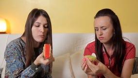De mooie jonge meisjes zitten op de laag en eten heerlijke cakes met sinaasappel en pistaches, kiwi Vriendschap stock footage