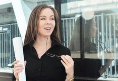 De mooie jonge meisjesingenieur verheugt zich bij de voltooiing van het project, die zich dichtbij het gebouw bevinden stock afbeeldingen