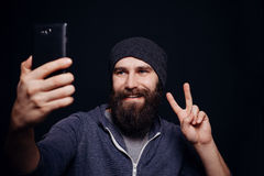 De mooie jonge mens met een baard maakt zelf Stock Foto's