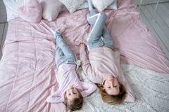 De mooie jonge moeder en haar weinig dochter liggen samen op het bed in de slaapkamer, spelen, koesteren en hebben pret royalty-vrije stock foto