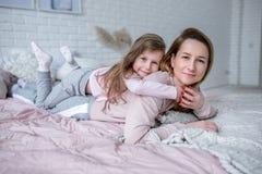 De mooie jonge moeder en haar weinig dochter liggen samen op het bed in de slaapkamer, spelen, koesteren en hebben pret royalty-vrije stock afbeeldingen