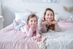 De mooie jonge moeder en haar weinig dochter liggen samen op het bed in de slaapkamer, spelen, koesteren en hebben pret stock afbeeldingen