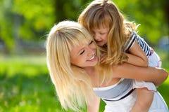 De mooie jonge moeder houdt haar weinig gelukkige daug royalty-vrije stock fotografie
