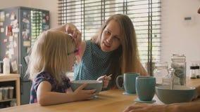 De mooie jonge moeder spreekt aan haar leuke blonde dochter bij ontbijt en het glimlachen Langzame mo stock videobeelden