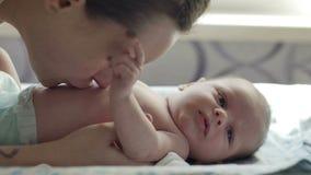De mooie jonge moederglimlach en kust haar kind stock videobeelden