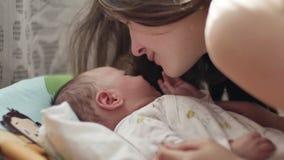 De mooie jonge moederglimlach en kust haar kind stock video