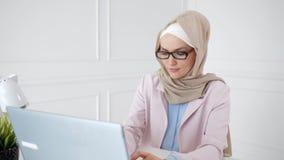 De mooie jonge moslimvrouw werkt aan laptop op haar werkplaats stock videobeelden