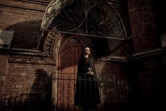 De mooie jonge non bevindt zich op portiek naast het verstand van de tempeldeur stock foto's