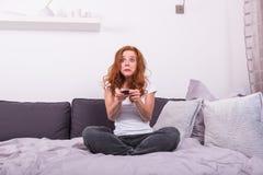 De mooie, jonge, redheaded vrouw is doen schrikken over het TV programma stock fotografie