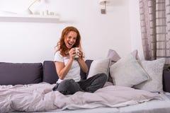 De mooie, jonge, redheaded vrouw geniet van haar koffie stock afbeelding