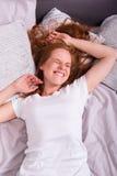 De mooie, jonge, redheaded vrouw geniet van haar tijd in bed royalty-vrije stock afbeeldingen