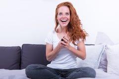 De mooie, jonge, redheaded vrouw glimlacht enthousiast stock afbeeldingen