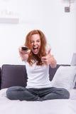 De mooie, jonge, redheaded vrouw houdt van het TV programma royalty-vrije stock afbeeldingen