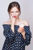 De mooie jonge retro pinupvrouw eet zoet die cakevoedsel op witte iinstudio wordt geïsoleerd stock afbeelding