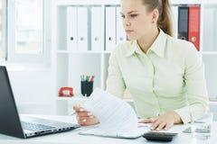 De mooie jonge secretaresse maakt nota's bekijkend laptop zitting op kantoor Stock Foto