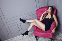 De mooie jonge sexy donkerbruine vrouw in zwarte baret en een korte zijdekleding rookt een sigaretzitting in roze leunstoel modie Royalty-vrije Stock Afbeeldingen