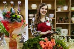 De mooie jonge smilling vrouwenbloemist gebruikt een tablet in bloemwinkel stock afbeeldingen