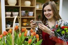 De mooie jonge smilling vrouwenbloemist neemt een beeld op haar smartphone in bloemwinkel stock foto