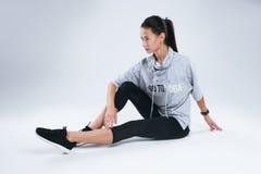De mooie jonge sportvrouw die yoga doen oefent terwijl het zitten op de witte achtergrond in studio uit Stock Foto's