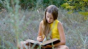 De mooie jonge tiener leest een boek stock videobeelden