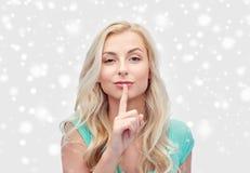 De mooie jonge vinger van de vrouwenholding bij haar lippen royalty-vrije stock afbeeldingen