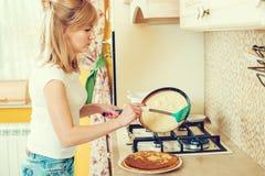 De mooie jonge vrouw bereidt pannekoeken in de keuken voor stock afbeeldingen