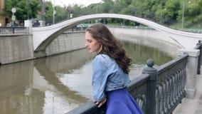 De mooie jonge vrouw in blauwe kleding bevindt zich op een rivierbank stock video