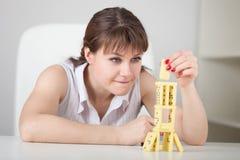 De mooie jonge vrouw bouwt toren van domino's Royalty-vrije Stock Afbeelding