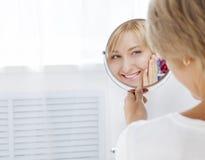De mooie jonge vrouw in de ochtend, kijkt in de spiegel Stock Foto