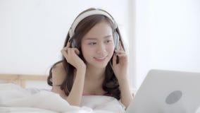 De mooie jonge vrouw die van Azië in slaapkamer liggen die laptop computer met behulp van ontspant luistert muziek, meisje die vi stock videobeelden