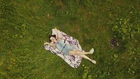 De mooie jonge vrouw die van de hemelmening op gras in de zomerdag liggen stock footage
