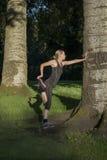De mooie jonge vrouw doet in openlucht oefeningen in park royalty-vrije stock afbeeldingen