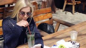 De mooie jonge vrouw drinkt cocktail in koffie stock footage