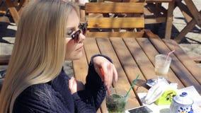 De mooie jonge vrouw drinkt cocktail in koffie stock video