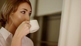 De mooie jonge vrouw drinkt een kop thee of een koffie stock videobeelden