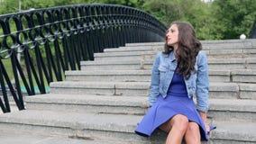 De mooie jonge vrouw in een blauwe kleding zit op stappen stock video