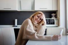 De mooie jonge vrouw in een comfortabele sweater zit in de keuken gebruikend een videogesprek in de boodschapper royalty-vrije stock afbeelding