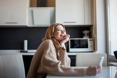 De mooie jonge vrouw in een comfortabele sweater zit in de keuken gebruikend een videogesprek in de boodschapper stock fotografie