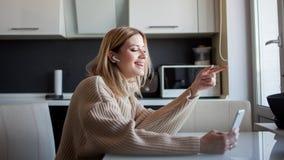De mooie jonge vrouw in een comfortabele sweater zit in de keuken gebruikend een videogesprek in de boodschapper stock afbeeldingen