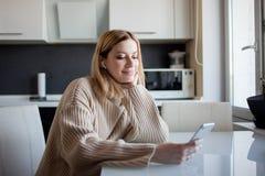 De mooie jonge vrouw in een comfortabele sweaterzitting in de keuken gebruikt de abonnementsdiensten en media toepassingen royalty-vrije stock afbeeldingen