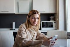 De mooie jonge vrouw in een comfortabele sweaterzitting in de keuken gebruikt de abonnementsdiensten en media toepassingen stock foto's