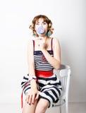 De mooie jonge vrouw in een gestreepte kleding eet een lolly royalty-vrije stock foto's