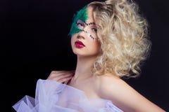 De mooie jonge vrouw in een groen geheimzinnig Venetiaans masker een nieuw jaar Carnaval, Kerstmismaskerade, een dansclub Stock Afbeelding