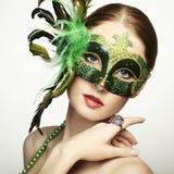 De mooie jonge vrouw in een Venetiaans masker stock afbeeldingen